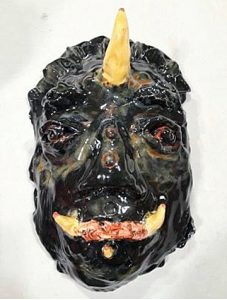 A glossy black ceramic mask depicting a mythical creature half human half dinosaur with orange horns
