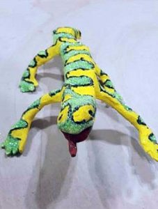 A yellow & green billowing patterned ceramic sculpture of a lizard with its tongue sticking out, painted with acrylic paint and glitter