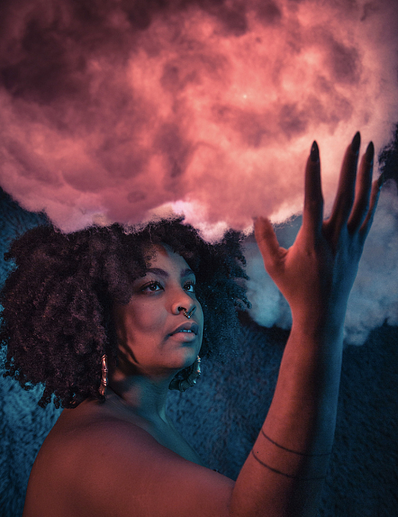 Color photo of Arielle gray, with her hand reaching towards a cloud above her head, which is backlit in shades of pink.
