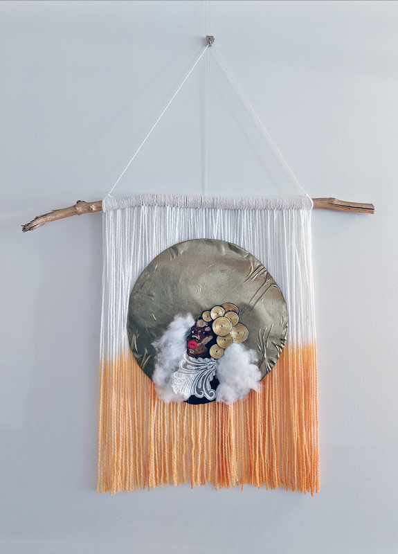 """Photo of a piece titled \""""Woman as God\"""", made of white and orange yarn hanging from a branch. In the middle is a circle covered in gold fabric, and in the middle of it is a soft sculpture of a black woman made of felt, embroidery floss, gold thread and lace."""