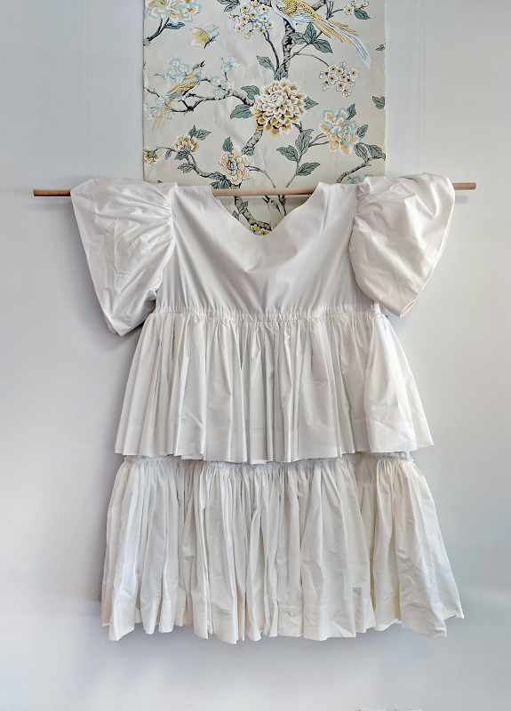 A white cotton dress with a wide boat neck, puffy sleeves and layered double skirt hangs from a pole, with a strip of floral wallpaper behind.