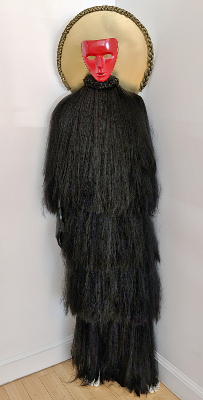 ""\""""Uneasy Deity"""" is a mannequin covered in layers of synthetic braiding hair made to resemble a Mende masked dancer. The face is a red mask over a gold circle surrounded with a gold braid.""407|800|?|en|2|1b6ac677f7d3fb8628ece4fd89118fd6|False|UNLIKELY|0.29002800583839417