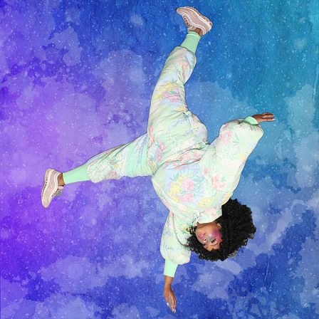 Photo of Arielle Gray wearing a space suit made out of an old floral comforter. The artist floats upside down over a blue and purple speckled background meant to resemble space.