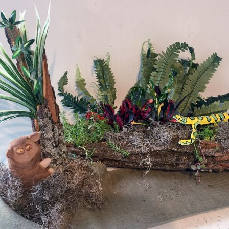 Frontispiece, floral and plant arrangement with wood log planter, ceramic lizard, and ceramic tarsier monkey.