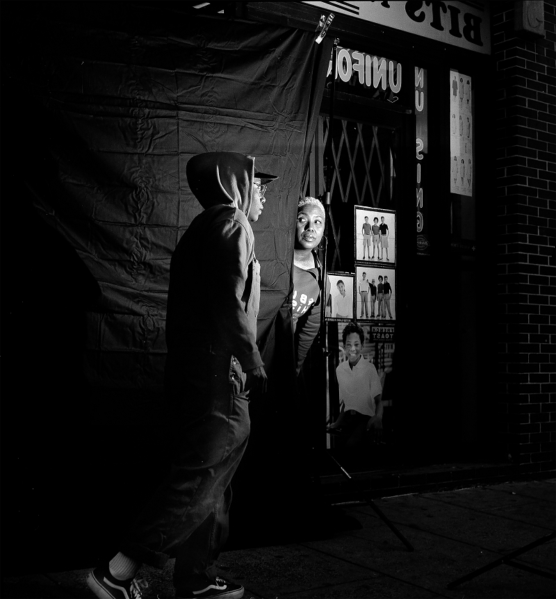 Black and white photo of person wearing a hoodie walking past another person looking out at them from behind a black curtain
