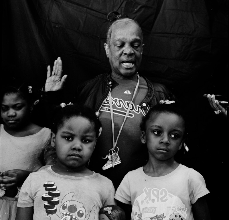 Black and white photo of a middle aged black male lifting his right hand. Three young girls stand in front of him.