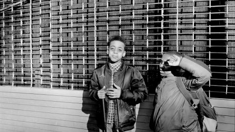 Black and white photograph of two black boys in front of a metal store fence