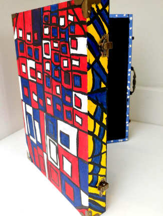 Wooden box standing on its side, open, painted in square patterns in red, blue, yellow and white.