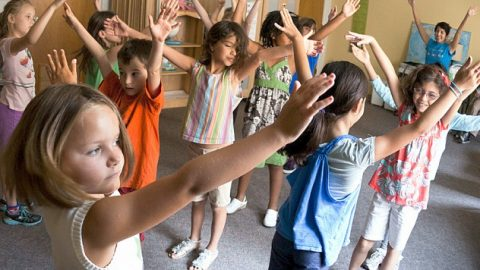 Young students standing and reaching with their arms up