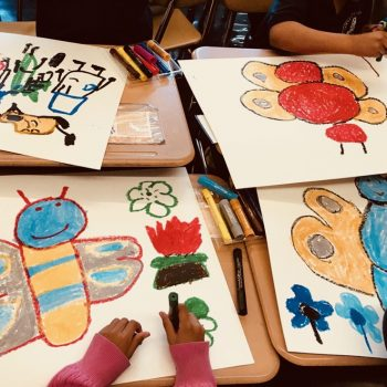 Close up of four children's art work of colorful insects made with pastels