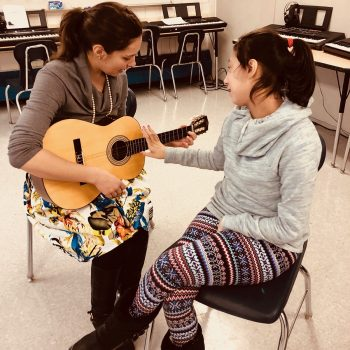 Teenage girl sitting, watching and reaching her hand towards her female teacher, who is playing the guitar