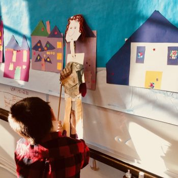 Young child playing with a handmade puppet of a person. In the background is a mural with houses made of collaged paper.
