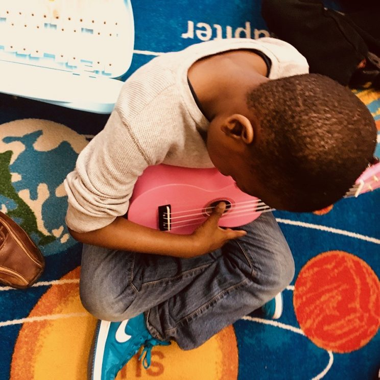 Young child sitting on a rug playing a pink ukulele