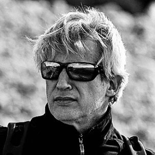 Man with short gray hair, wearing sunglasses and a zippered black sweater.