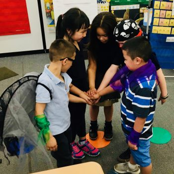 Five young children, some wearing props, stand in a semi-circle and join their hands together.