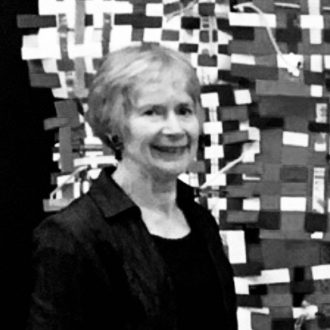 Woman with short gray hair, smiling. In the background is a woven mural