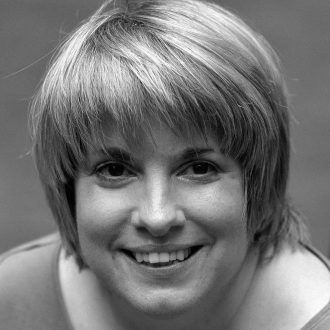 Woman with short blond hair and bangs, smiling
