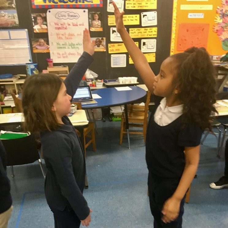 Two students face each other and raise their arms to connect their hands