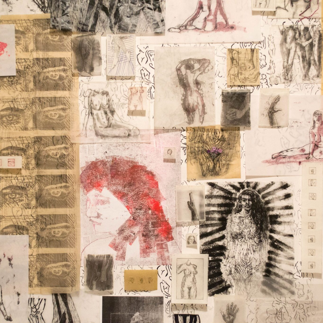 Multiple pieces of white and tan paper in different sizes featuring balck and red sketches of bodies, body parts, and faces are layered over each other on a wall using pins.