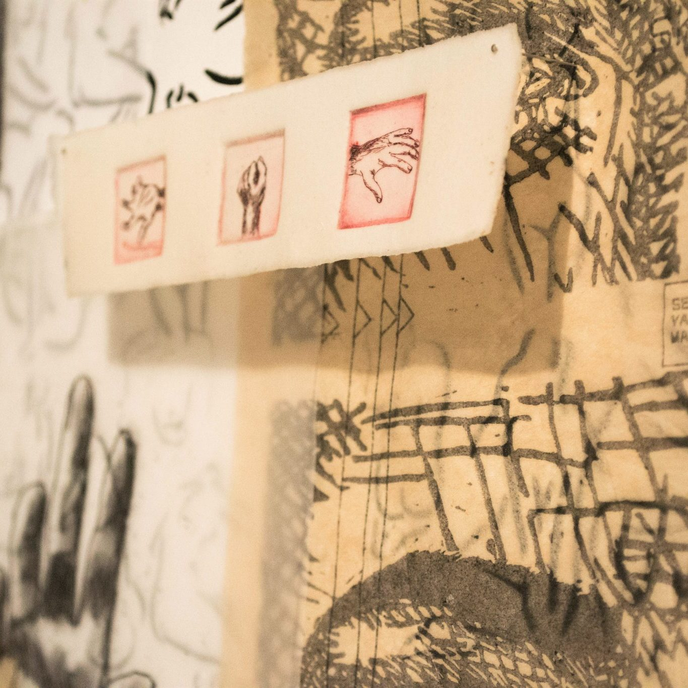 Pieces of paper with black and red pen sketches of bodies and body parts are layered on a wall using small pins