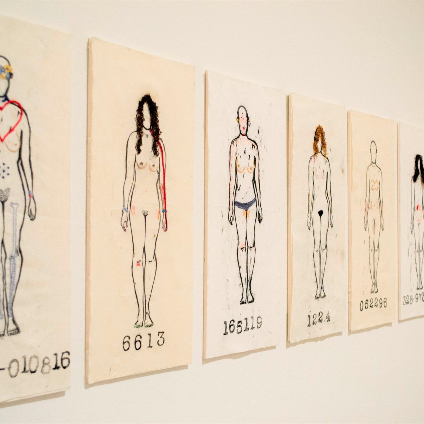 A row of 10 separate images of bodies outlines are embroidered in red and black hung side-by-side to form a horizontal line on the wall